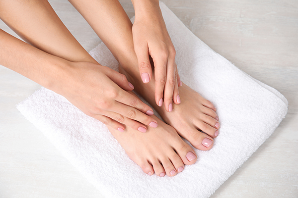 Woman touching her smooth feet on white towel, closeup. Spa trea